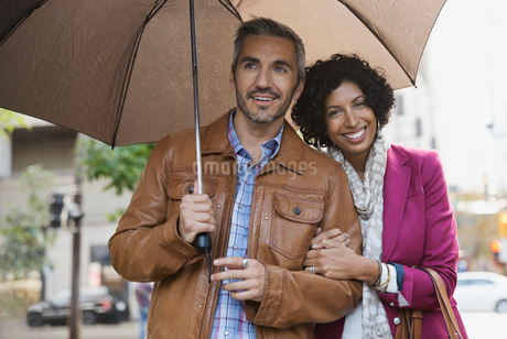 Portrait of couple standing outdoors with umbrellaの写真素材 [FYI02303553]