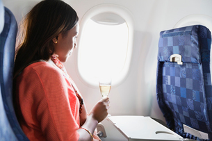Woman relaxing with a drink in airplaneの写真素材 [FYI02303590]