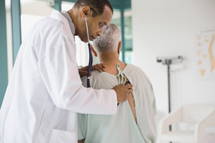 Male doctor checking senior patient with stethoscopeの写真素材 [FYI02303721]