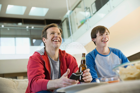 Father and son watching TV in living roomの写真素材 [FYI02303794]