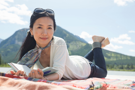 Portrait of mature woman reading on dockの写真素材 [FYI02303889]