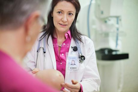 Mature female doctor explaining breast exam to senior patientの写真素材 [FYI02303900]