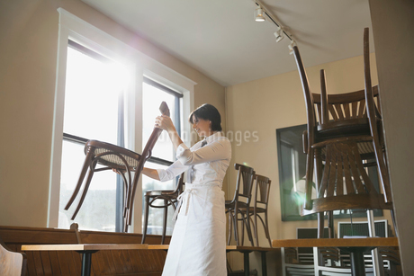 Waitress arranging chairs in coffee shopの写真素材 [FYI02304092]