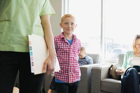 Dental assistant leading boy in lobbyの写真素材 [FYI02304279]