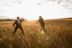 Businessmen fighting with sword and shield in fieldの写真素材 [FYI02304359]