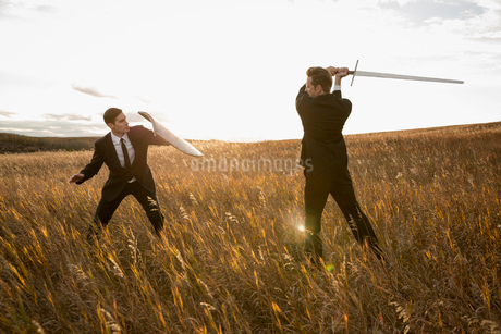 Angry businessmen fighting with sword and shield in fieldの写真素材 [FYI02304444]