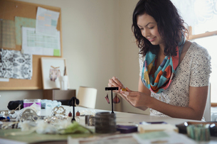 Young female artist making earrings in workshopの写真素材 [FYI02304471]