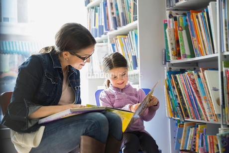 Mother and daughter reading book in bookstoreの写真素材 [FYI02304557]