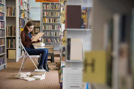 Bookstore worker with clipboard checking inventoryの写真素材 [FYI02304569]