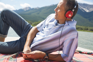 Portrait of mature man listening to music on dockの写真素材 [FYI02304588]