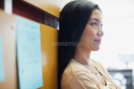 Businesswoman leaning on wall in officeの写真素材 [FYI02304677]