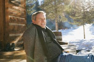 Smiling man relaxing outside log cabinの写真素材 [FYI02304745]