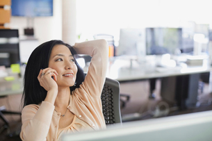 Businesswoman using mobile phone at desk in officeの写真素材 [FYI02304789]