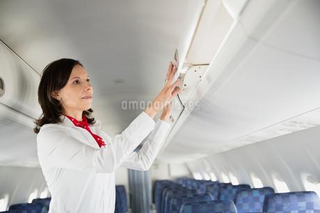 Flight attendant closing overhead bin in airplaneの写真素材 [FYI02304852]