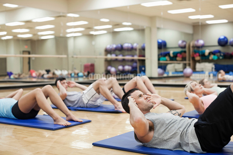 Group of people doing sit-ups in fitness classの写真素材 [FYI02304869]