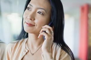 Businesswoman using smartphone in officeの写真素材 [FYI02304984]