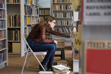 Bookstore worker with clipboard checking inventoryの写真素材 [FYI02305073]
