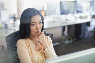 Businesswoman looking at computer in officeの写真素材 [FYI02305159]
