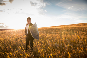 Aggressive businessman with sword and shield in fieldの写真素材 [FYI02305247]