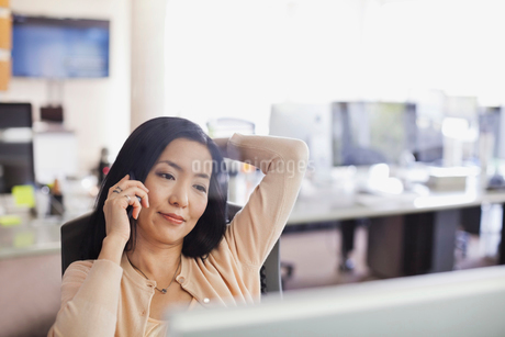 Businesswoman using mobile phone at desk in officeの写真素材 [FYI02305268]