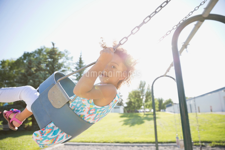 Portrait of little girl swinging at parkの写真素材 [FYI02305325]