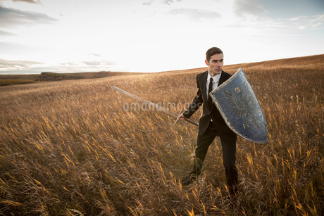 Alert businessman with sword and shield outdoorsの写真素材 [FYI02305469]