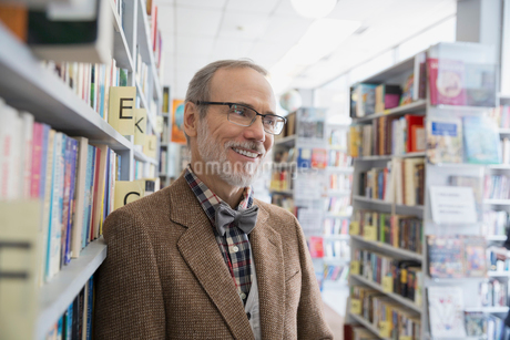 Smiling bookstore owner leaning on shelfの写真素材 [FYI02305486]