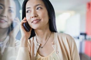 Businesswoman using smartphone in officeの写真素材 [FYI02305558]