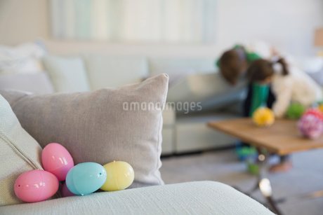 Colorful Easter eggs behind cushion on sofaの写真素材 [FYI02305726]