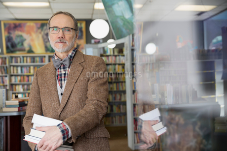 Portrait of man holding books in bookstoreの写真素材 [FYI02305734]
