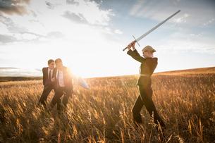 Businesswoman attacking businessmen with sword in fieldの写真素材 [FYI02305851]