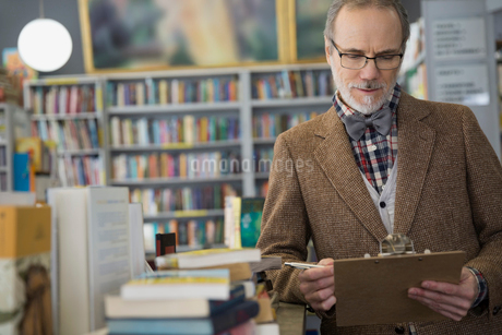 Bookstore owner with clipboard taking inventoryの写真素材 [FYI02305857]