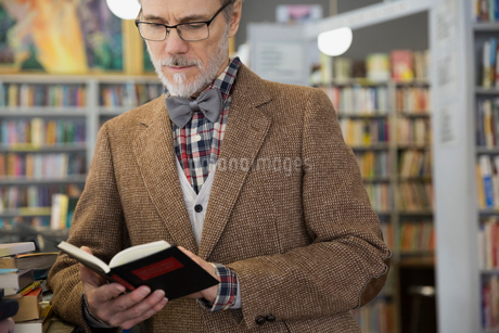 Man in bowtie reading book in bookstoreの写真素材 [FYI02305933]