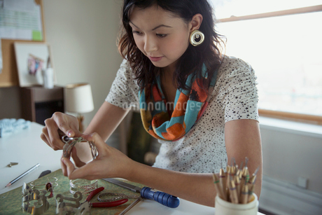 Beautiful female artist making bracelets at deskの写真素材 [FYI02305985]