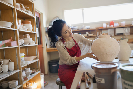 Female potter analyzing pot in studioの写真素材 [FYI02306107]