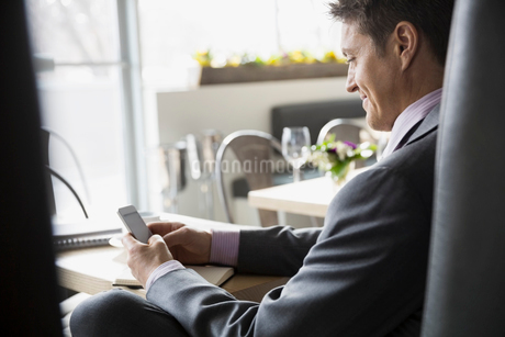Businessman texting with cell phone at bistro tableの写真素材 [FYI02306188]