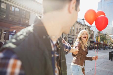 Smiling woman leading man down city streetの写真素材 [FYI02306192]