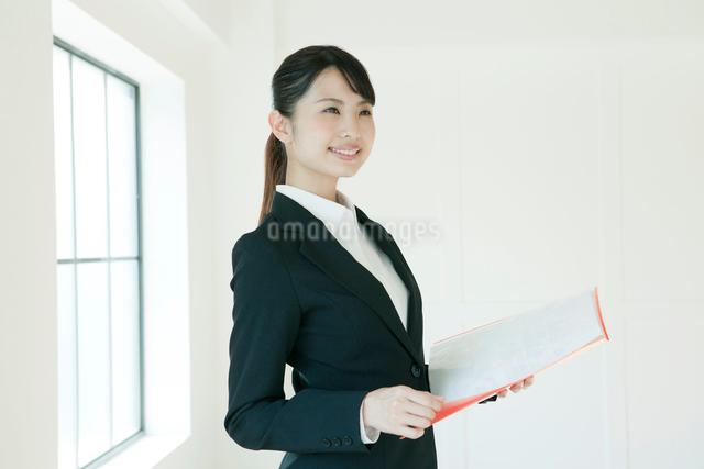 ファイルを持った、スーツ姿の若い女性の写真素材 [FYI02306384]