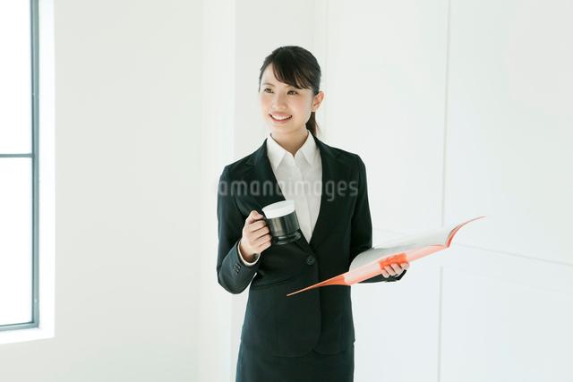 珈琲とファイルを持った、スーツ姿の若い女性の写真素材 [FYI02306418]
