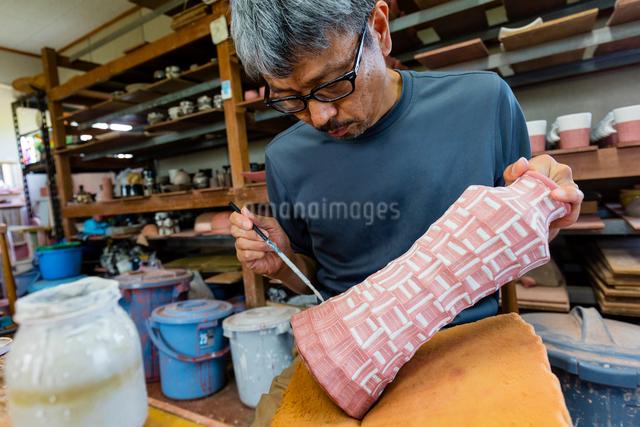 素焼きの陶器に絵付けする陶芸家の写真素材 [FYI02306449]