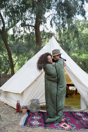 Playful couple sharing sleeping bag outside camping yurtの写真素材 [FYI02306542]