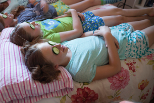 Girls relaxing with cucumbers on eyes at slumber partyの写真素材 [FYI02306650]