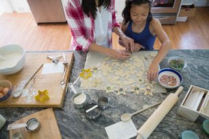 Mother and daughter using star cookie cutters on dough baking in kitchenの写真素材 [FYI02306829]