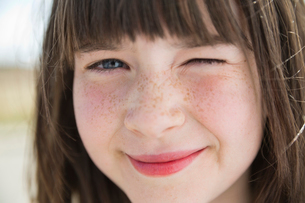 Close-up of little girl winking outdoorsの写真素材 [FYI02306948]