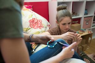 Girls making jewelry in bedroomの写真素材 [FYI02306964]