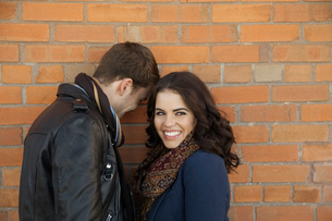 Smiling couple standing against brick wallの写真素材 [FYI02306970]