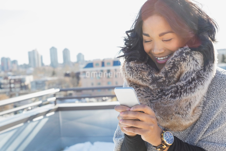 Woman in cozy scarf using smart phone outdoorsの写真素材 [FYI02307079]