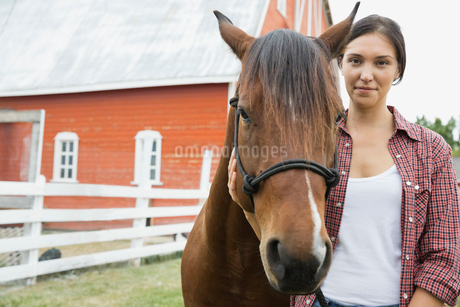 Portrait of beautiful woman with horse on farmの写真素材 [FYI02307111]