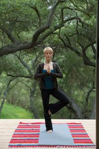 Serene woman practicing yoga tree pose on deckの写真素材 [FYI02307201]