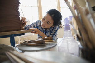Female student working on clay sculpture in art classの写真素材 [FYI02307205]